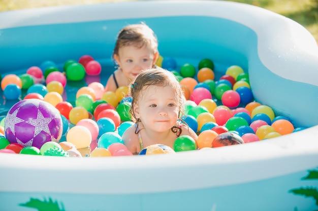 Las dos niñas jugando con juguetes en la piscina inflable en el día soleado de verano