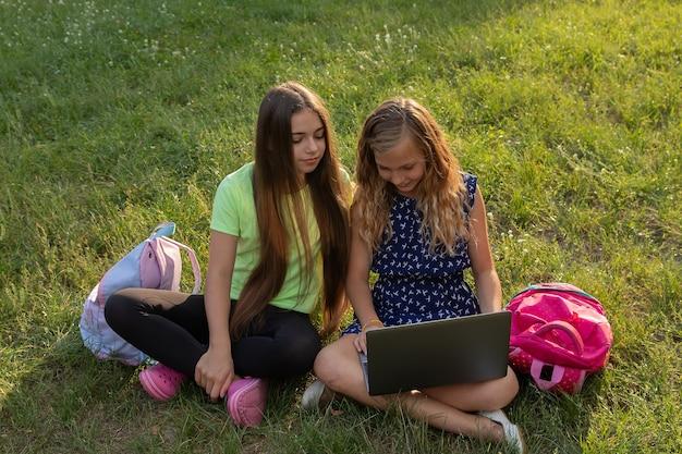 Dos niñas con laptop y maletines haciendo los deberes o divirtiéndose mientras están sentados en el césped afuera