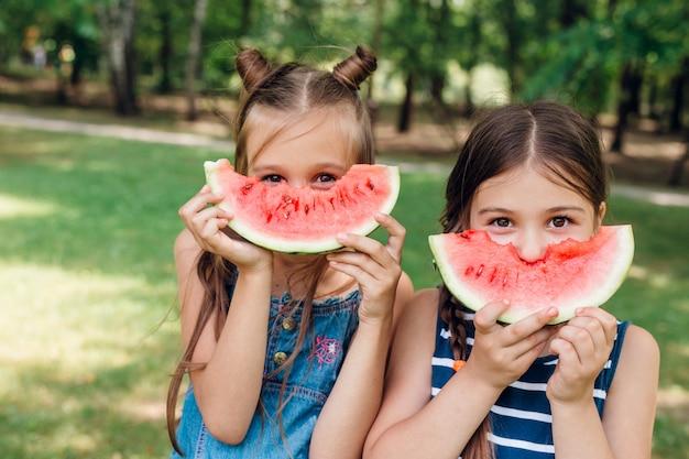 Dos niñas lindas comiendo sandía en el parque en verano