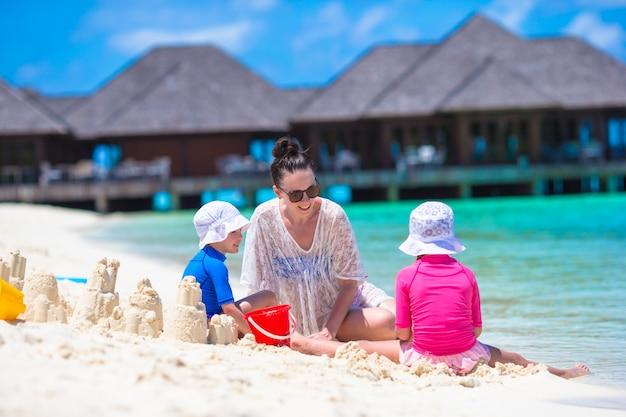 Dos niñas y una madre feliz jugando con juguetes de playa en vacaciones de verano