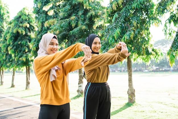 Dos niñas musulmanas con velo estiran las manos antes de trotar y practicar deportes al aire libre en el parque