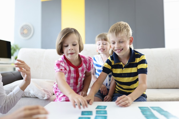 Dos niñas y un niño se sientan en el sofá y juegan un juego de mesa