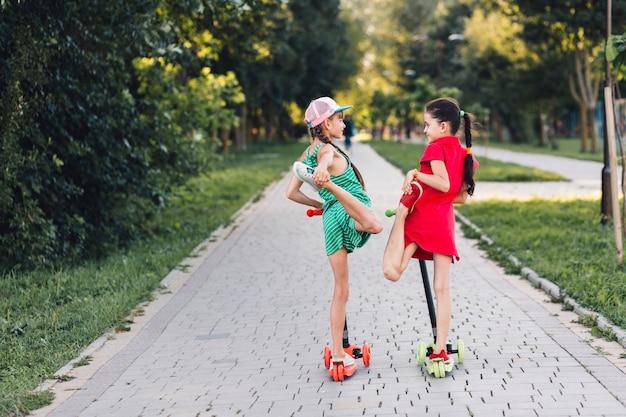 Dos niñas de pie sobre el patinete scooter estirando sus piernas