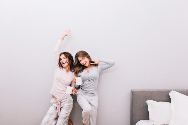 Dos niñas en pijama con tazas en la pared gris. se estiran y sonríen.