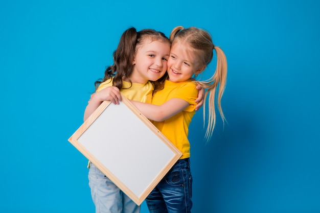 Dos niñas sonriendo con un tablero de dibujo vacío sobre un fondo azul.