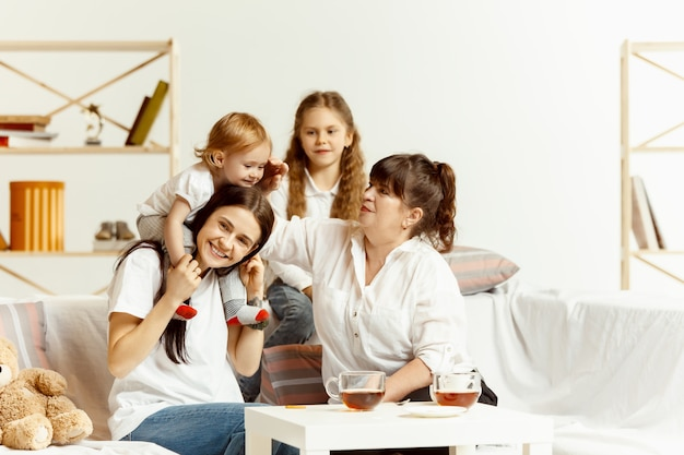 Dos niñas, su atractiva madre joven y su encantadora abuela sentados en el sofá y pasar tiempo juntos en casa. generación de mujeres. día internacional de la mujer. feliz día de la madre.