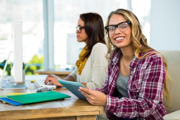 Dos niñas trabajan en la oficina en computadora y tableta
