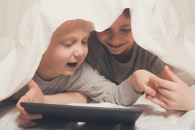 Dos niños acostados y mirando algo en una tableta.