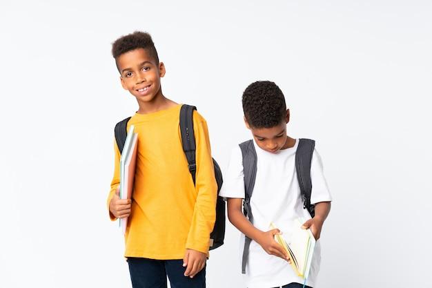 Dos niños afroamericanos estudiantes fondo blanco
