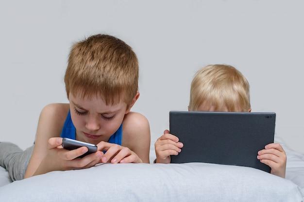 Dos niños con aparatos están acostados en la cama. los niños usan teléfonos inteligentes y tabletas