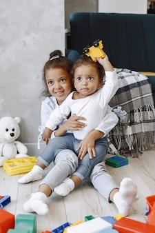 Dos niños bonitos se sientan en el suelo y juegan con juguetes cerca del sofá. hermanas afroamericanas jugando en casa.