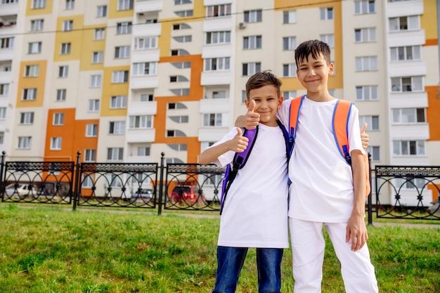 Dos niños en edad escolar se abrazan en la calle camino a la escuela