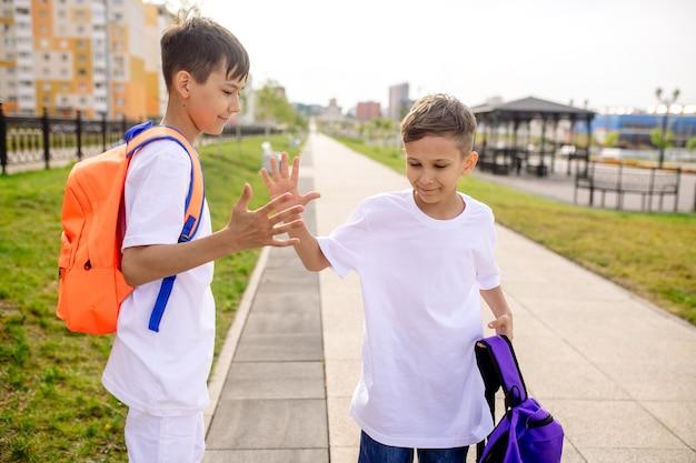 Dos niños escolares van a la escuela con mochilas brillantes.