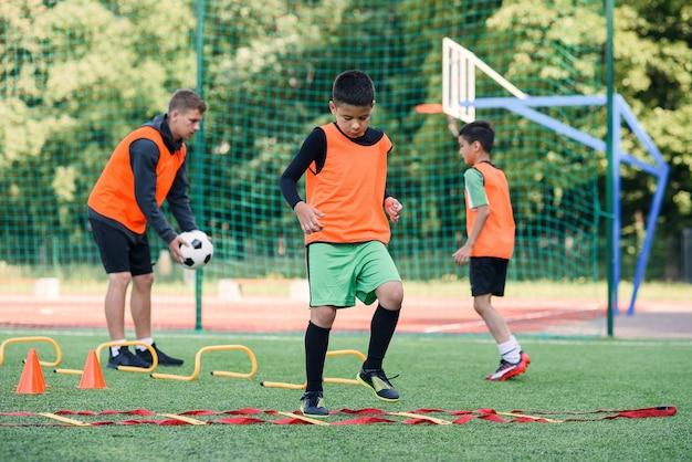 Dos niños de la escuela están ejecutando ejercicios de escalera durante el campamento de verano de fútbol.