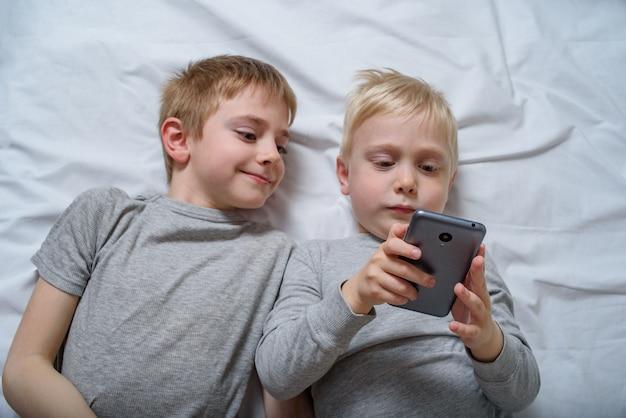 Dos niños están acostados en la cama con un teléfono inteligente. ocio gadget
