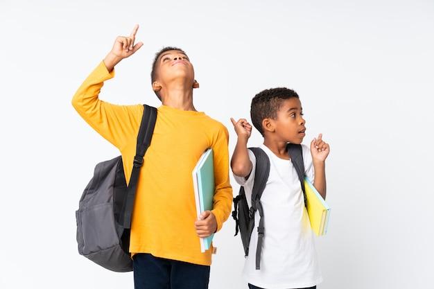 Dos niños estudiantes afroamericanos fondo blanco y apuntando hacia arriba