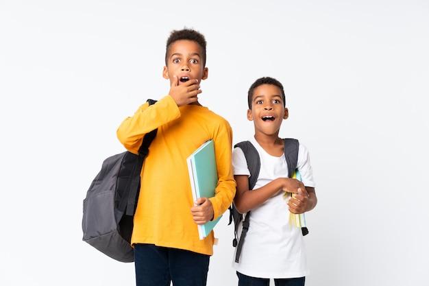 Dos niños estudiantes afroamericanos sobre blanco aislado haciendo gesto de sorpresa