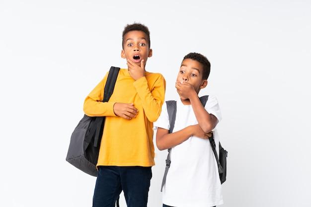 Dos niños estudiantes afroamericanos sobre pared blanca aislada haciendo gesto de sorpresa