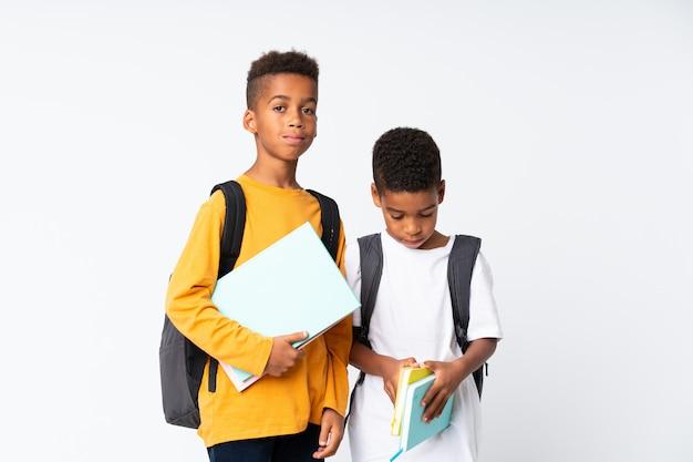 Dos niños estudiantes afroamericanos sobre pared blanca aislada