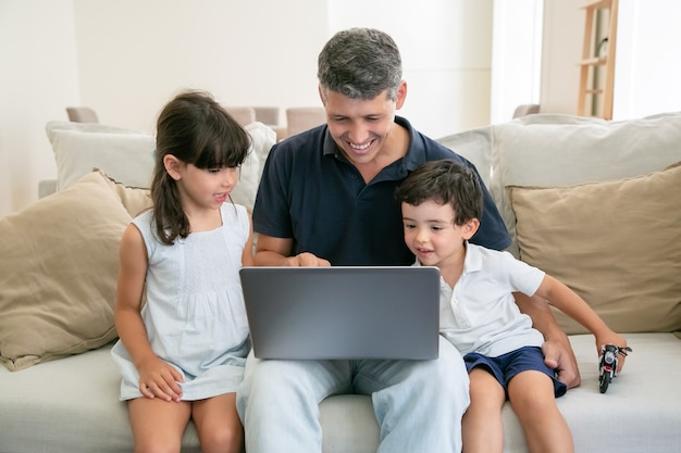 Dos niños felices y su papá usando la computadora portátil mientras están sentados en el sofá en casa, mirando la pantalla.