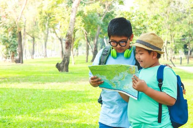 Dos niños se fueron de excursión sostengan el mapa del mundo para aprender y estudiar