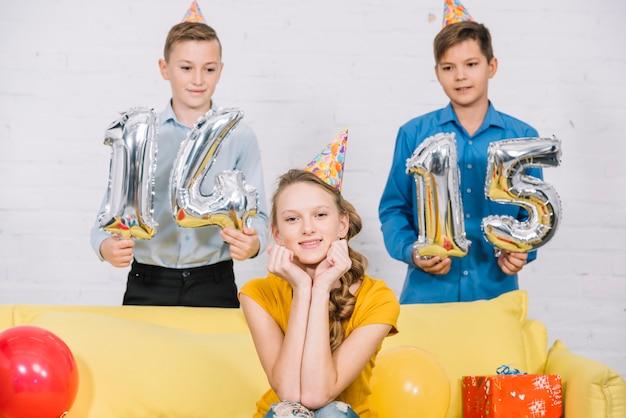 Dos niños con globos numéricos 14 y 15 en la mano de pie detrás de la cumpleañera