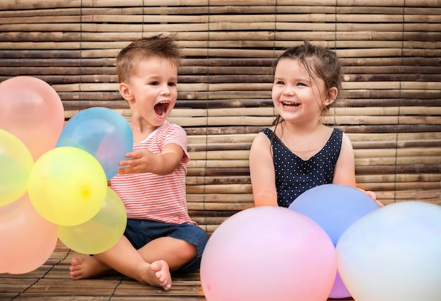 Dos niños con globos en el piso de madera.