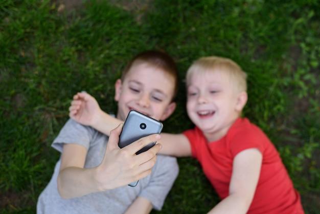 Dos niños hacen selfie en un teléfono inteligente mientras está acostado en la hierba. vista superior