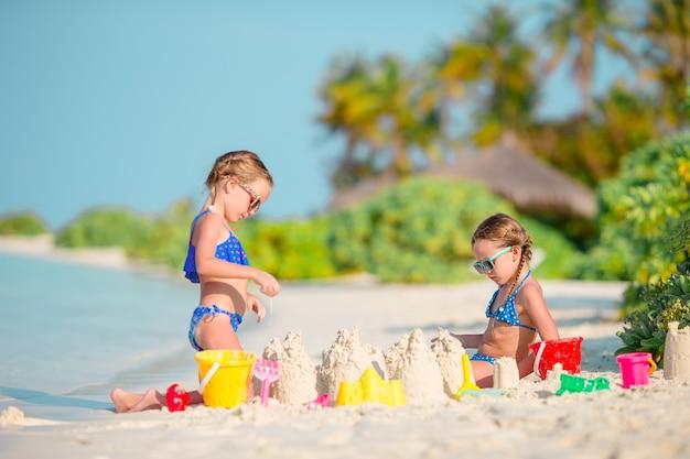 Dos niños haciendo castillos de arena y divirtiéndose en la playa tropical