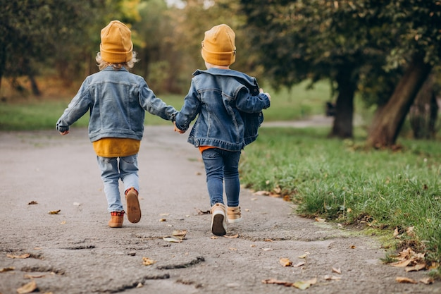 Dos niños hermanos corriendo en un parque de otoño
