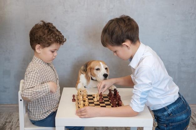 Dos niños juegan al ajedrez en una mesa. un perro beagle está viendo el juego de una manera divertida. juegos de mesa en el círculo familiar.
