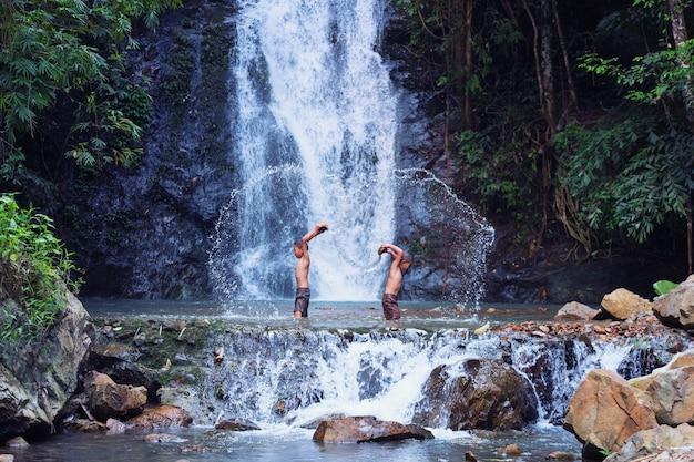 Dos niños juegan y ríen de la pesca en la cascada