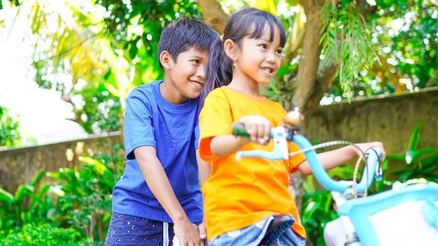 Dos niños jugando en bicicleta en el jardín detrás de la casa.