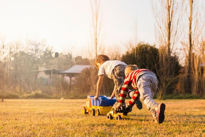 Dos niños jugando con vehículos de juguete en la hierba verde