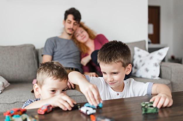 Dos niños jugando con juguetes de coche sobre escritorio de madera