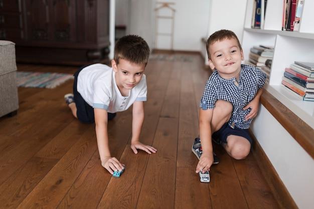 Dos niños jugando con juguetes de coches en el piso de madera dura
