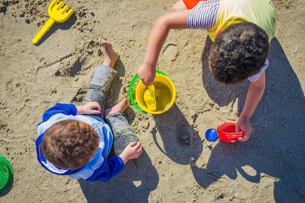 Dos niños jugando sobre arena con juguetes de playa