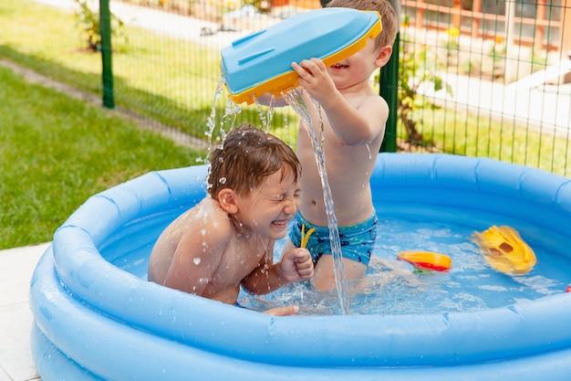 Dos niños con juguetes en la piscina.