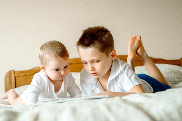 Dos niños, leyendo un libro, educándose