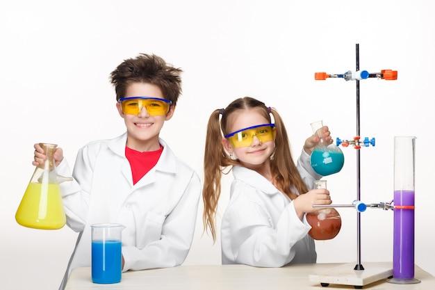 Dos niños lindos en la lección de química haciendo experimentos