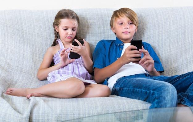 Dos niños mirando a los teléfonos inteligentes en el sofá
