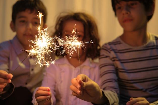 Dos niños y una niña fuera de foco con destellos brillantes en primer plano