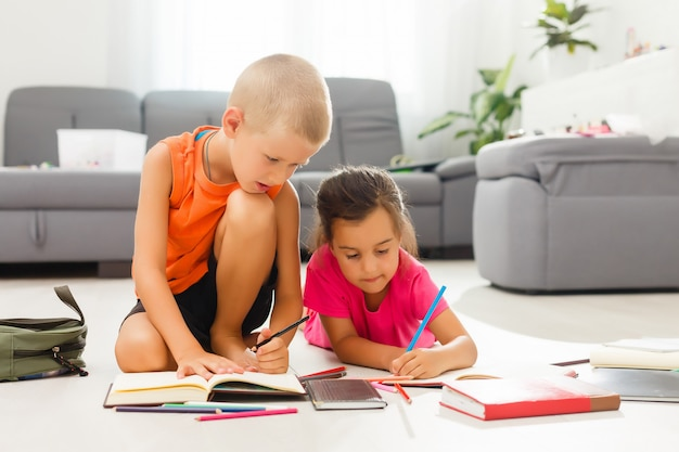 Dos niños, niñas de edad preescolar mirando tableta en casa en el piso