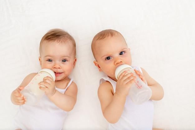 Dos niños, un niño y una niña gemela de 8 meses beben leche de un biberón en la cama en la guardería, alimentan al bebé, concepto de comida para bebés, vista superior,
