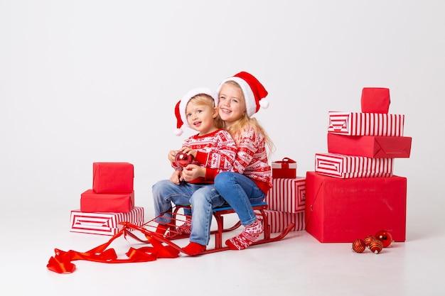 Dos niños, un niño y una niña con suéteres y gorros santa se sientan en un trineo para llevar regalos. estudio, fondo blanco, espacio para texto