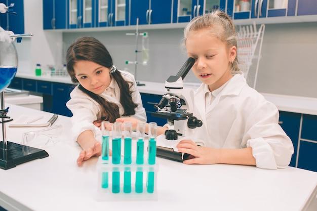Dos niños pequeños en bata de laboratorio que aprenden química en laboratorio de la escuela. jóvenes científicos en gafas protectoras haciendo experimentos en laboratorio o gabinete químico. mirando a través del microscopio