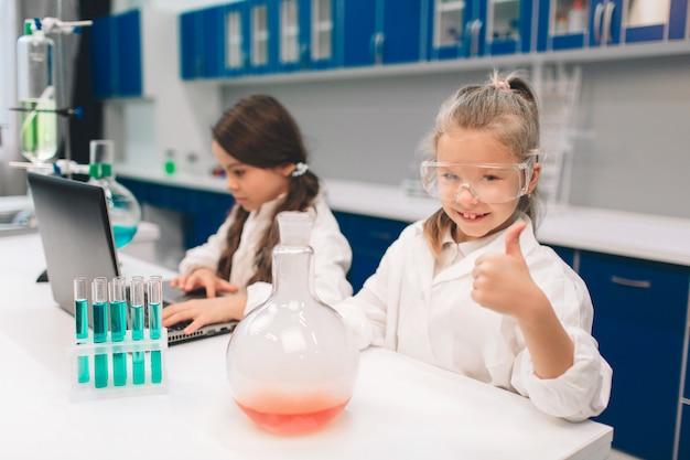 Dos niños pequeños en bata de laboratorio que aprenden química en laboratorio de la escuela. jóvenes científicos en gafas protectoras haciendo experimentos en laboratorio o gabinete químico. pulgares hacia arriba