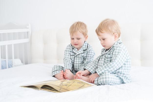 Dos niños pequeños bebés gemelos en pijama libro de lectura sentado en la ropa de cama blanca en la cama