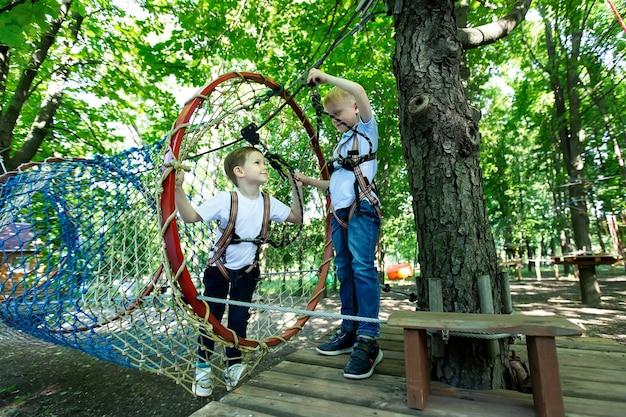 Dos niños pequeños en equipo de escalada están caminando por un camino de cuerdas en un parque de aventuras, sosteniendo una cuerda y un mosquetón.