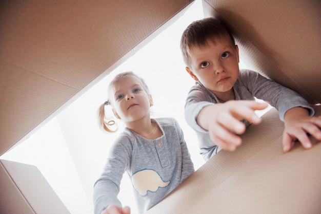 Dos niños pequeños, niño y niña, abriendo una caja de cartón y mirando dentro con sorpresa